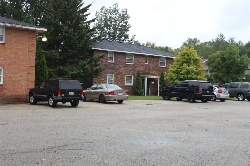 Front view of apartments with cars